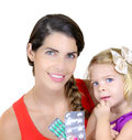 Portrait of happy young mother with her daughter closeup giving medicine to Stock Photography