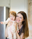 Portrait of happy Young mother with little baby girl in kitchen Royalty Free Stock Photo