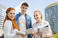 Portrait of happy young university students studying outdoors Royalty Free Stock Photo