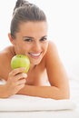 Portrait of happy young woman with apple laying on massage table in spa salon Stock Photos
