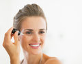 Portrait of happy young woman applying cosmetic serum in bathroom Stock Image