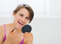 Portrait of happy young woman applying makeup Royalty Free Stock Photo