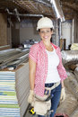 Portrait of a happy young woman architect wearing hardhat at construction site Royalty Free Stock Image
