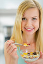 Portrait of happy young woman eating muesli Royalty Free Stock Photo