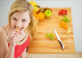 Portrait of happy young woman having a bite while cutting salad on board Royalty Free Stock Photo