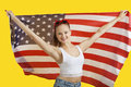 Portrait of happy young woman holding american flag over yellow background Royalty Free Stock Image