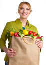 Portrait of happy young woman holding a bag shopping full groceries on white background Stock Photography