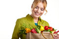 Portrait of happy young woman holding a bag shopping full groceries on white background Stock Photo