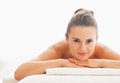 Portrait of happy young woman laying on massage table in spa salon Royalty Free Stock Photos