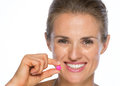 Portrait of happy young woman with pill Royalty Free Stock Photo