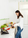 Portrait of a happy young woman preparing food i Royalty Free Stock Photography