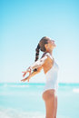 Portrait of happy young woman rejoicing at seaside in white swimsuit Royalty Free Stock Images