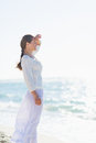 Portrait of happy young woman on sea shore looking into distance in white dress Stock Images