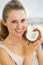 Portrait of happy young woman showing coconut high resolution photo Royalty Free Stock Photography