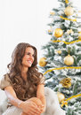 Portrait of happy young woman sitting near christmas tree in living room Royalty Free Stock Photos