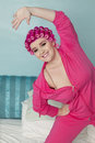 Portrait of happy young woman stretching while standing on bed Royalty Free Stock Photography