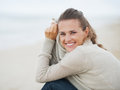 Portrait of happy young woman in sweater sitting on lonely beach with long hair Stock Images