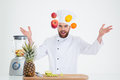 Portrait of a hapy male chef cook juggle with fruits Royalty Free Stock Photo