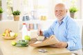 Portrait of healthy senior at breakfast sitting in kitchen holding newspaper looking camera smiling Stock Image