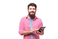 Portrait of a hipster man with beard using tablet computer and look at camera Royalty Free Stock Photo