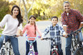 Portrait of hispanic family on cycle ride in countryside smiling to camera Stock Photography