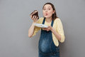 Portrait of a hungry pregnant woman eating sweet chocolate cake Royalty Free Stock Photo