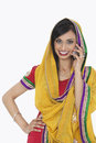 Portrait of an indian woman in traditional wear answering phone call over white background Royalty Free Stock Images