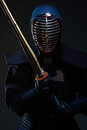 Portrait of a kendo fighter with shinai dark background Stock Image