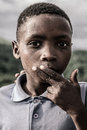 Portrait of a kid south africa coffee bay january on kids tribe village smiling to the camera with his finger on his month near to Royalty Free Stock Image