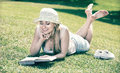 Portrait of l woman lying on green lawn in park and reading book Royalty Free Stock Photo