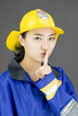 Portrait of a lady firefighter with finger on lips young attractive asian woman in her s shot in studio white background Royalty Free Stock Photos