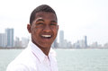 Portrait of a laughing guy at beach with skyline handsome young standing near the ocean the city in the background and laughs Stock Photos