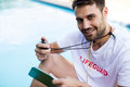 Portrait of lifeguard holding clipboard and stopwatch at poolside Royalty Free Stock Photo