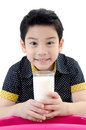Portrait of little asian boy drinking a glass of milk isolated on white background Royalty Free Stock Photos