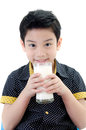 Portrait of little asian boy drinking a glass of milk isolated on white background Stock Photos