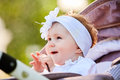 Portrait of the little baby girl sitting in a children`s carriage in summer day. Royalty Free Stock Photo