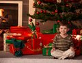 Portrait of little boy with christmas tree sitting on floor in front and presents smiling Stock Image
