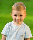 Portrait of little boy on green grass field Royalty Free Stock Photo