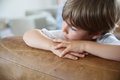 Portrait of little boy leaning on sofa looking away Royalty Free Stock Photo
