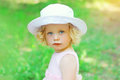 Portrait of little curly girl child wearing a white hat Royalty Free Stock Photo