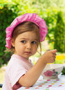 Portrait of little cute girl in a purpule cap eats with appetite a breakfast from a plate with the drawn flower in outdoor cafe Royalty Free Stock Photo