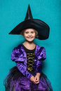 Portrait of little girl in black hat and witch clothing. Halloween. Fairy. Tale. Studio portrait on blue background