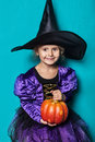 Portrait of little girl in black hat and witch clothing with pumpkin. Halloween. Fairy. Tale. Studio portrait on blue background