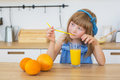 Portrait of a little girl in a blue dress drinks an orange juice and thinks