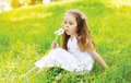 Portrait of little girl child on the grass blowing white flowers Royalty Free Stock Photo
