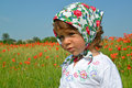 Portrait of the little girl in a colorful kerchief against red poppies Royalty Free Stock Photo