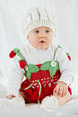 Portrait of little girl dressed in strawberry suit sitting on white coverlet Royalty Free Stock Photo