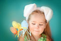 Portrait of a little girl in easter bunny ears cute dressed holding colorfull eggs Stock Photography