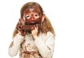 Portrait of a little girl eating chocolate bar and face covered in chocolate Royalty Free Stock Photo