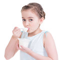 Portrait of a little girl eating yogurt isolated on white Royalty Free Stock Image